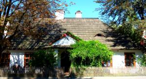 Przepiękny biały dworek z filarami z przodu i dachem pokrytym gontem - drewniany dach. Dworek otoczony olbrzymią ilością zieleni, porośnięty pnączem przed wejściem duże zielone drzewo. na wejściu powiewa flaga Polski. Ogrodzenie z drewnianych sztachetek.