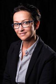 zdjęcie prof. Moniki Bogdanowskiej. uśmiechnięta kobieta, w okularach, z krótko ściętymi ciemnymi włosami, o delikatnych rysach twarzy. Ubrana w koszulę z biało-niebieskie prążki i czarną marynarkę.