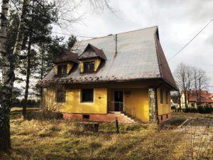na zdjęciu budynek w kolorze zółtym z dachem pokrytym falistą blachą.